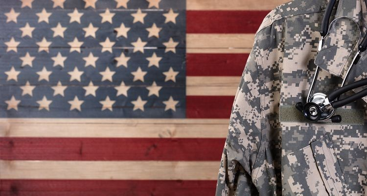 Military nurse standing in front of an American Flag background
