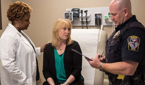 police officer filing out report with female forensic nurse and female patient
