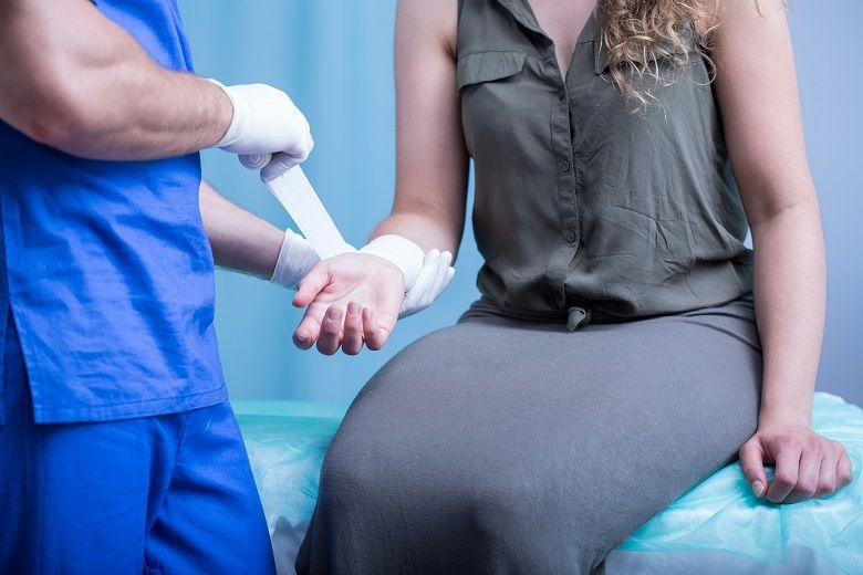 nurse wrapping women's wrist in bandages