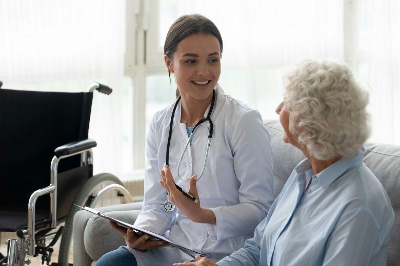 female nurse talking with elderly female patient