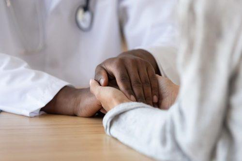A nurse practitioner holds a patient's hands.