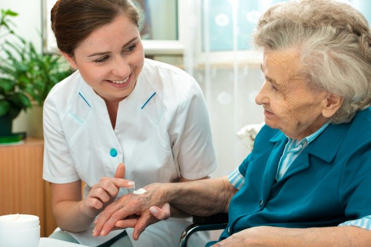 Nurse assists elderly woman with skin care as part of personalized attention