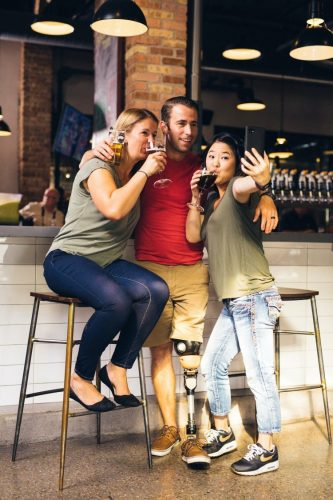 Three college students are taking a selfie while drinking beers in an off-campus bar.