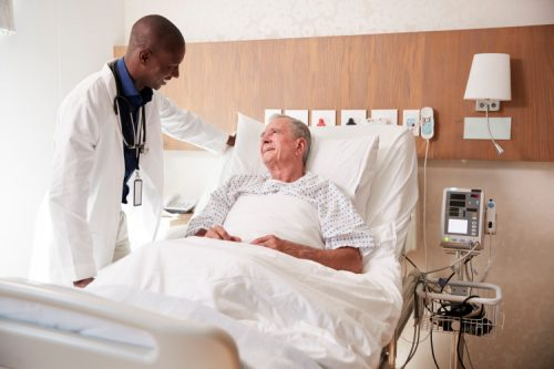 An adult-gerontology nurse practitioner talks with a patient in a hospital bed.