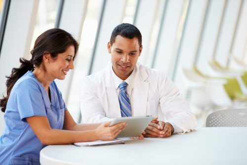 A nurse practitioner and a doctor sit at a table discussing a treatment plan.