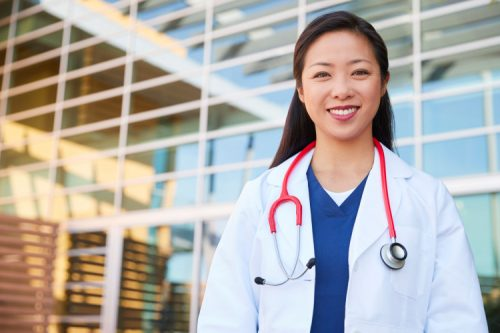 A smiling nurse practitioner stands outside of a hospital.