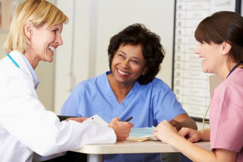 A DNP-prepared nurse educator sitting and talking with two nurses.
