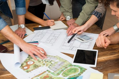 Hands pointing out project designs on graph paper