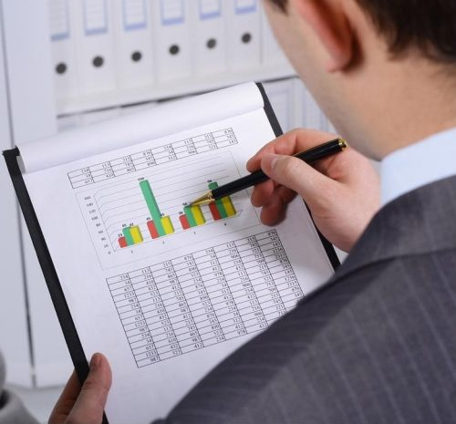 An accountant studies figures on a graph