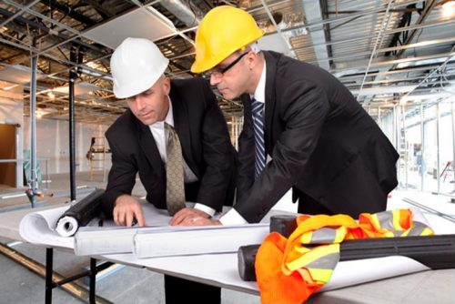 A site supervisor reviews construction progress with a cost estimator.