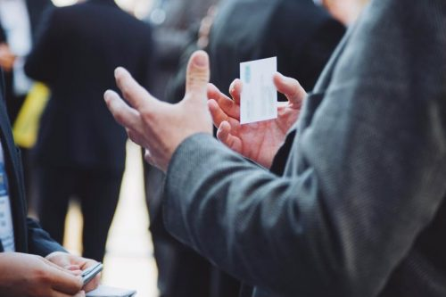 A man holding a business card at a networking event.