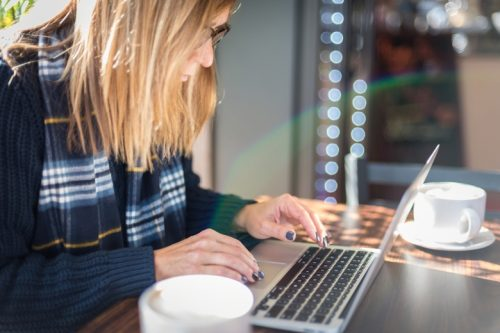 woman with glasses working on laptop at coffee shop with latte.
