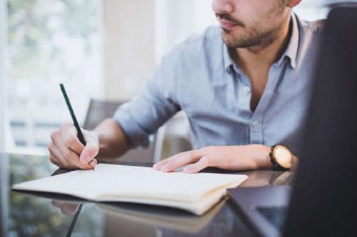 A man writes in a notebook while seated at his desk.