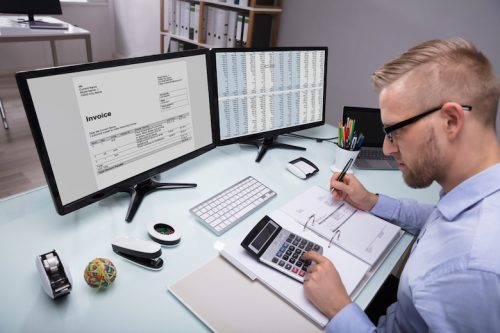 An accountant looks at an invoice and numbers on computer monitors