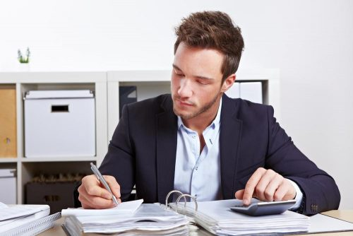 Credit analyst working through pile of paperwork