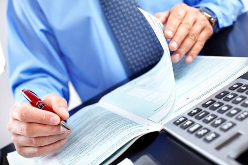 A corporate accountant fills out a tax form