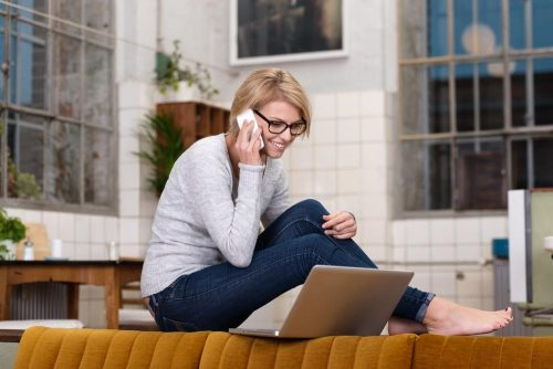 Young, savvy-looking woman sitting near a laptop, while using a cell phone.
