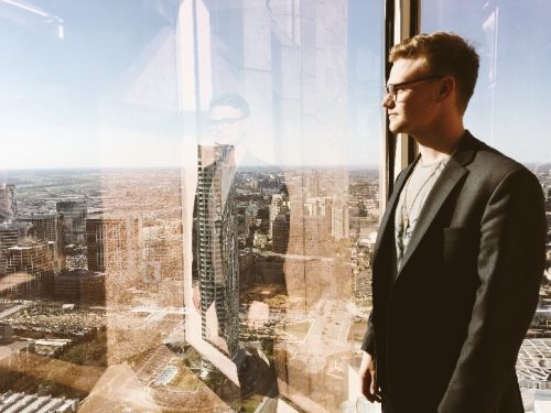 Man in professional dress staring out the window of a high-rise at a city.