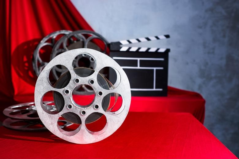 A film reel and clapboard symbolize the entertainment industry
