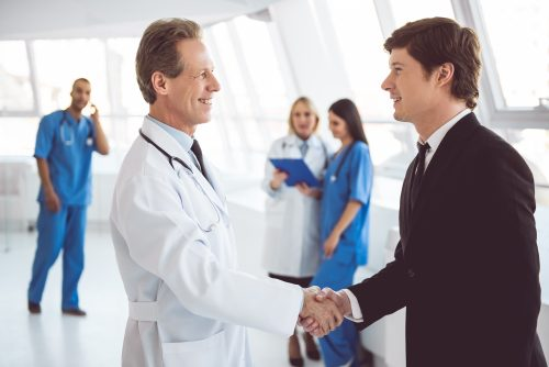 A Healthcare MBA Salary Administrator Shaking Hands With a Doctor.
