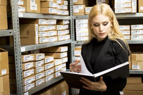 A logistician examines inventory records in a warehouse.