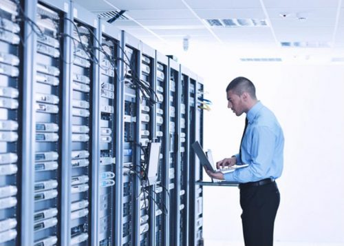 An information security analyst works in a server room.