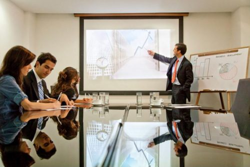 A management accountant presents data to executives.