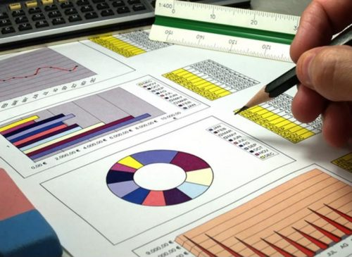 A senior data analyst works with printed data visualizations
