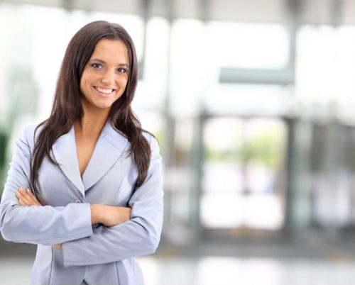 A confident businesswoman with her MBA stands in a lobby