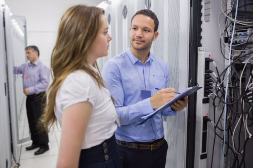 Information security analysts help with an issue in a data center.