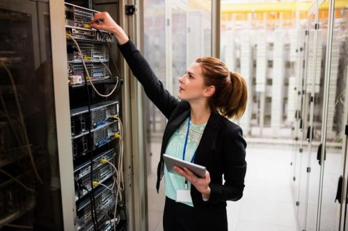 An information systems manager inspects a server