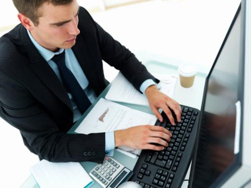 An information security analyst studies data on a PC