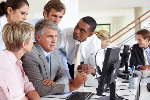 Businessmen and women in office huddled around desk looking at a computer monitor