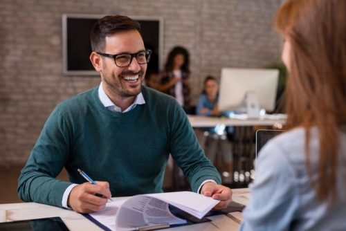 An accountant with glasses smiling at a client in an office space.