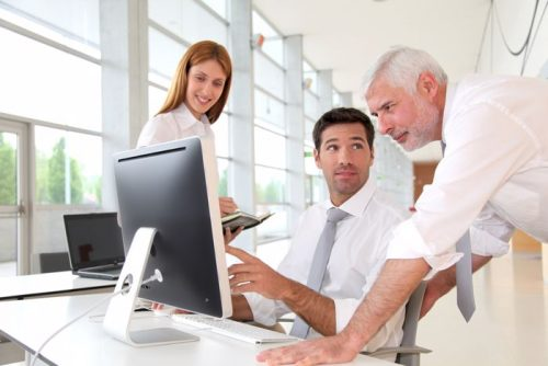 Businesswoman and two sales managers interacting around a desktop computer