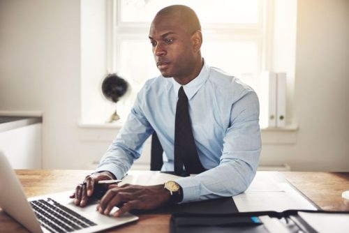 Accountant man in blue dress shirt and black tie on laptop