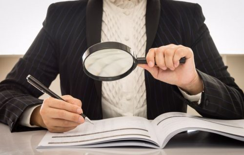 Accounting professional in white sweater and sports coat holding magnifying glass over workbook