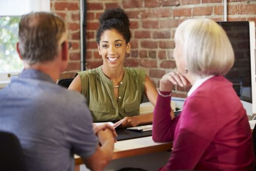 Accountant woman smiling while wearing green blouse, speaking with older couple