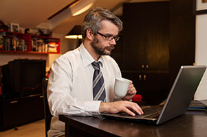 Man working on laptop and drinking a cup of tea