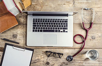 Laptop still on a rustic desk with medical equipment around it