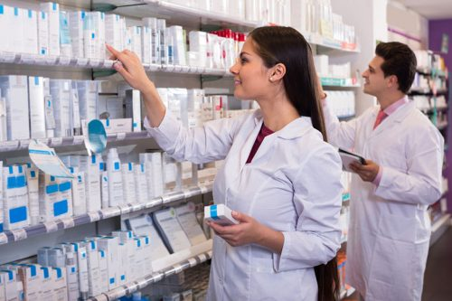 Pharmacist looking at medicine on a shelf