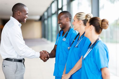 Health Informatics Consultant shaking hands with hospital staff
