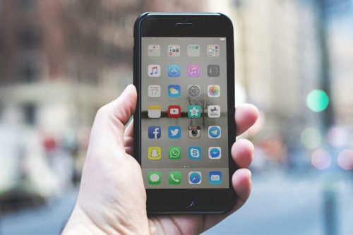 A person holds up an iPhone with different apps on the screen