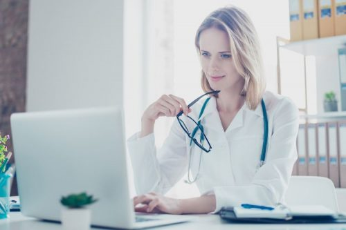 Physician uses health IT to check patient information.