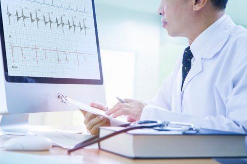 A health informatics analyst studies data on a computer screen.