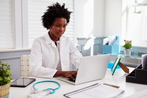 A healthcare worker types on a laptop at her desk.