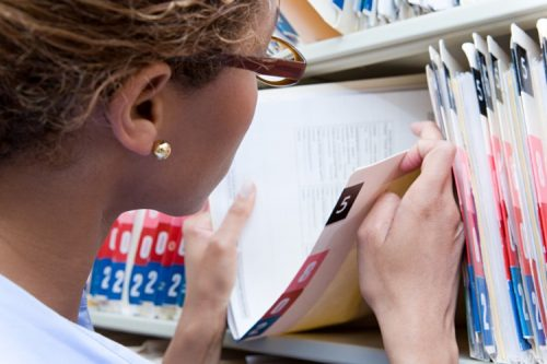 A medical facility administrator opens a patient file folder on a shelf.