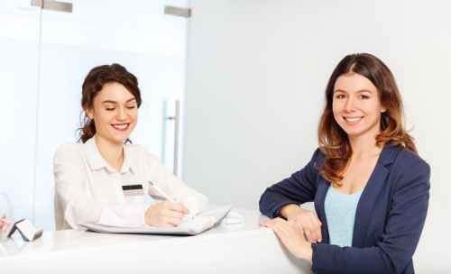 A smiling female health information manager gathers information from a young female patient at a hospital admissions desk.