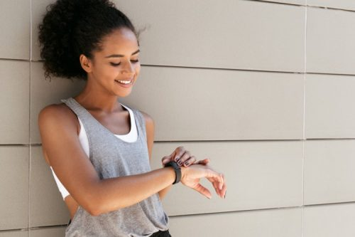 A young woman consults her fitness tracker watch.