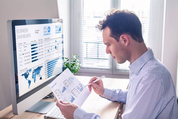 Data analyst reviews over data charts for his business.